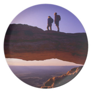 A couple watches sunrise from atop Mesa Arch in Plate