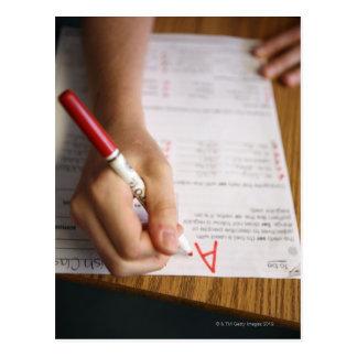 A middle school teacher puts a grade on a postcard