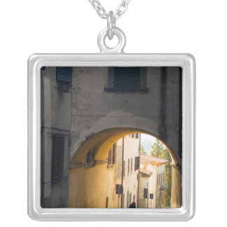 A person walking under an arch, down a hill in silver plated necklace