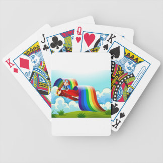 A plane with a young boy and a rainbow in the sky bicycle playing cards