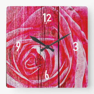 A rose image on a grungy wood panel square wall clock