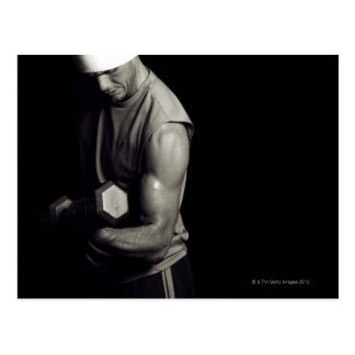 A young man lifts weights. postcard