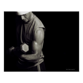 A young man lifts weights. poster