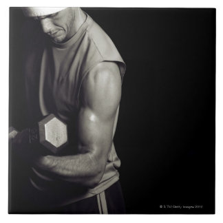 A young man lifts weights. tile