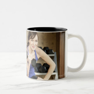 An active female lifting weights in a private mug