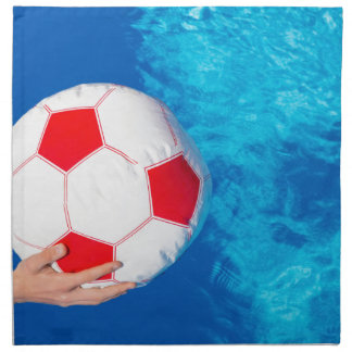 Arms holding beach ball above swimming pool water napkin