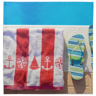 Bathing slippers and bath towel at swimming pool napkin