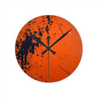 Black paint splatter on orange round clock