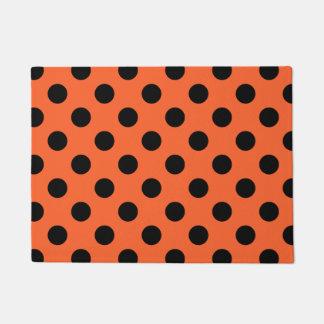 Black polka dots on orange doormat