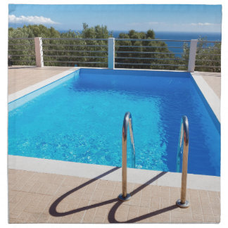 Blue swimming pool with steps at sea napkin