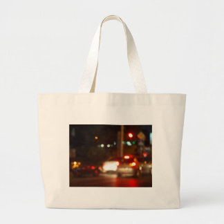 Blur and defocused lights on the stream of cars large tote bag