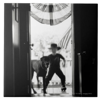 Blurred young boy and dog on porch tile