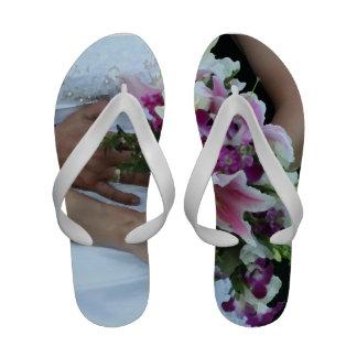 bride holding flowers groom behind painting flip flops