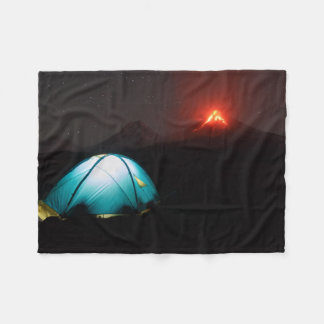 Camping at night on background of active volcano fleece blanket