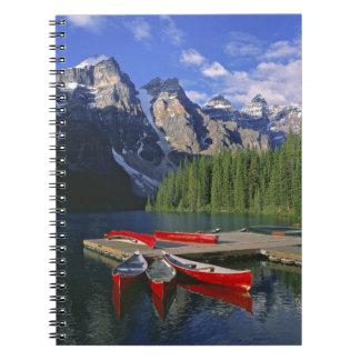 Canada, Alberta, Moraine Lake. Red canoes await Notebooks