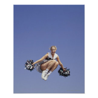 Cheerleader jumping, low angle view, portrait poster