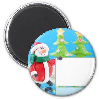 Clay snowman in winter wonderland holding a sign 6 cm round magnet