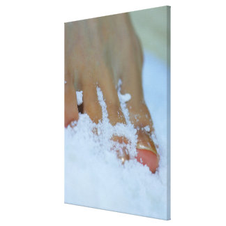 Close-up of a woman's foot in salt canvas prints
