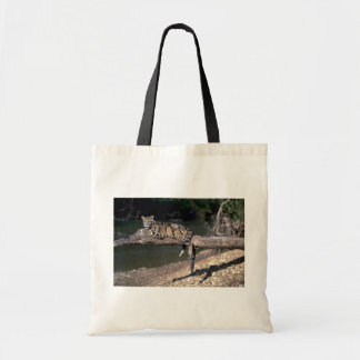 Clouded leopard on log tote bags