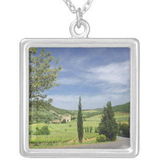 Country road curving between cypress trees in silver plated necklace