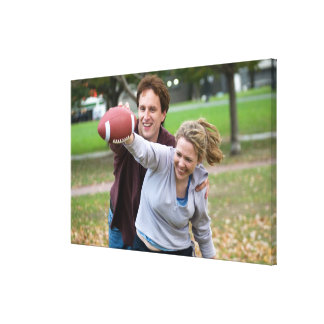 Couple playing football in park canvas prints