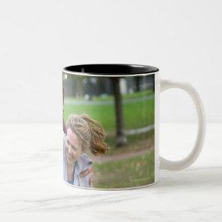 Couple playing football in park coffee mug