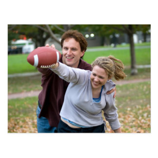 Couple playing football in park postcard