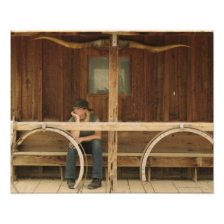 Cowgirl sitting on ranch porch poster
