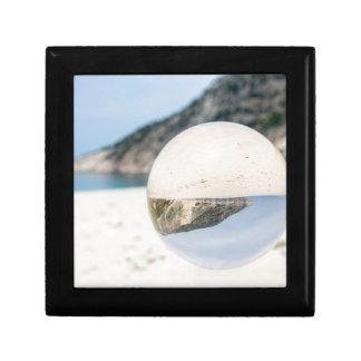 Crystal ball on sandy greek beach gift box