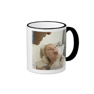 Dentist looking at patients teeth coffee mugs