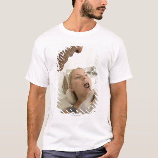 Dentist looking at patients teeth T-Shirt