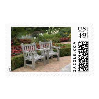 Empty wooden chairs along a garden path postage