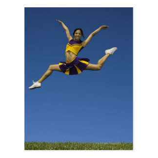 Female cheerleader jumping in air, arms postcard