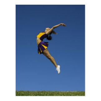 Female cheerleader jumping in air, side view postcard