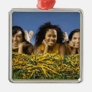 Female cheerleaders lying on grass with pompoms christmas ornament