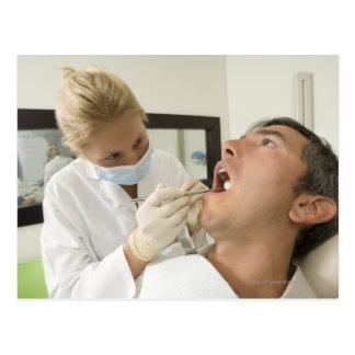 Female dentist examining man postcard