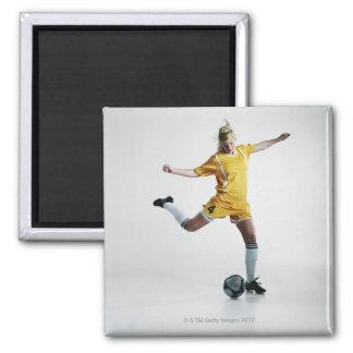 Female soccer player preparing to kick soccer magnet