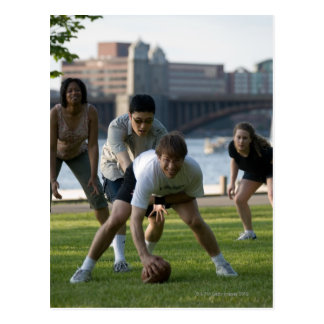 Friends playing game of football post card