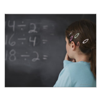 Girl looking at math equations on blackboard poster