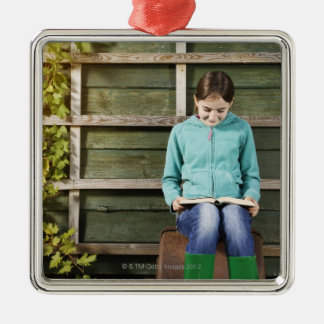 Girl sitting and reading book near vine christmas ornament