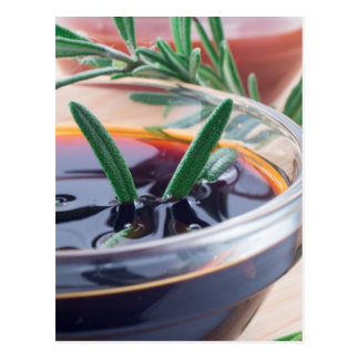 Glass cup with soy sauce and rosemary postcard