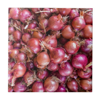 Heap of red onions on market tile