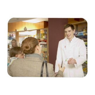 Male pharmacist handing medicine over to young vinyl magnet