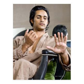 Man admiring his manicure postcard