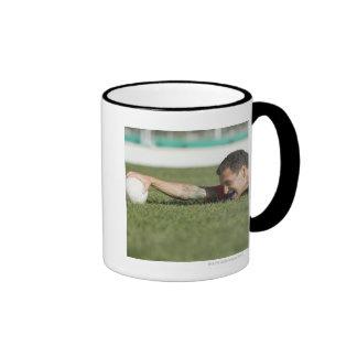 Man grabbing rugby ball mugs