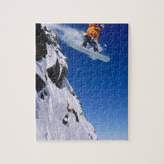 Man on a snowboard jumping off a cornice at jigsaw puzzle