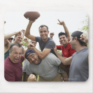 Man raising soccer ball celebrating with friends mouse pad