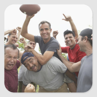Man raising soccer ball celebrating with friends square sticker
