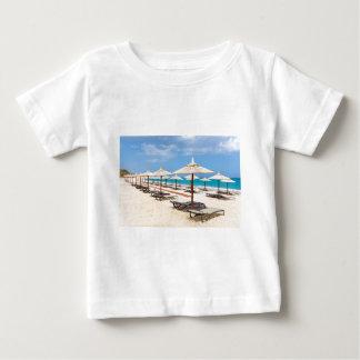 Many reed beach umbrellas in a row  on empty beach baby T-Shirt