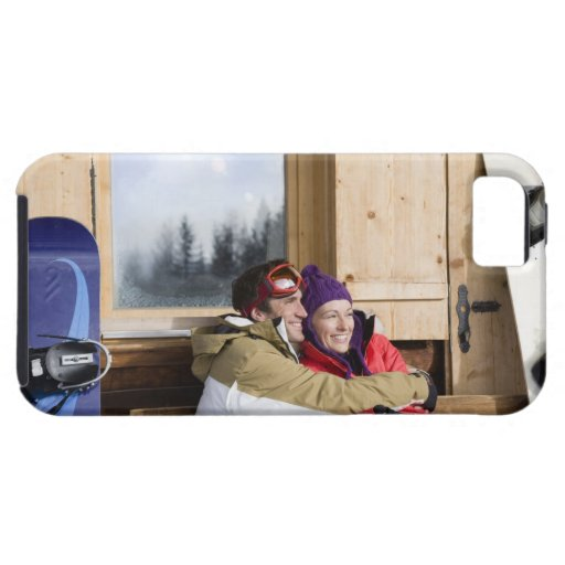 Mid adult couple embracing outside log cabin iPhone 5 cover